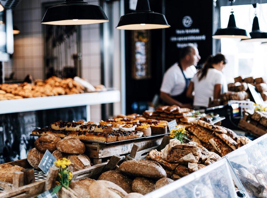Na imagem, vários pães quentinhos e bolos são dispostos em um balcão, enquanto os donos do empreendimento estão ao fundo.