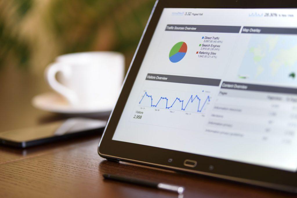 Em cima de uma mesa, um tablet mostra gráficos com dados sobre um aluguel por temporada.