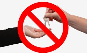 Na imagem, um sinal de proibido sobre um homem entregando uma chave após alugar.