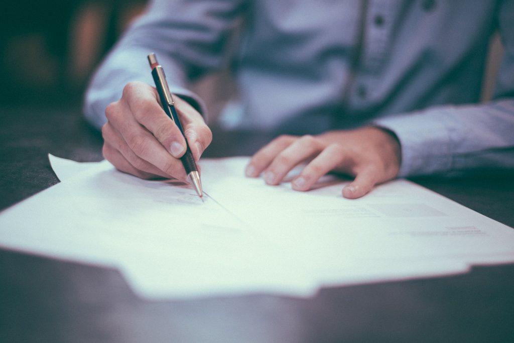 Na imagem, um homem assina um contrato de aluguel por temporada.